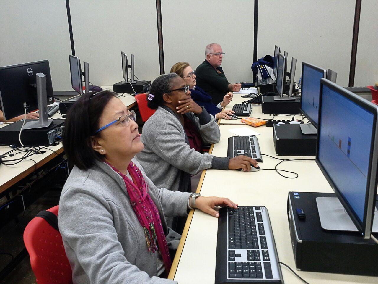 Quatro alunos durante a aula do curso Cérebro Ativo, estão em frente aos computadores